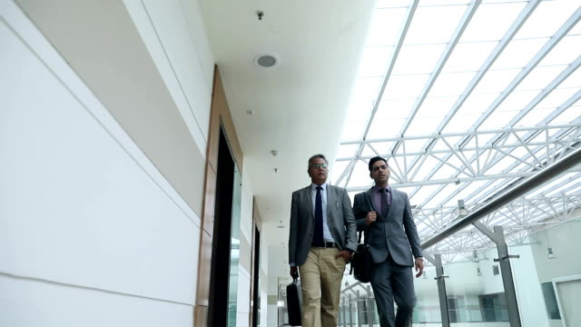 Two businessmen walking in the office, Delhi, India