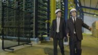 MS TS two businessmen walking through industrial installation, talking and gesturing, RED R3D 4K