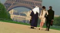 CANTED REAR VIEW two businessmen (1 Arab) + woman walking toward Eiffel Tower / Paris
