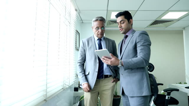 Two businessmen working on digital tablet in the office, Delhi, India
