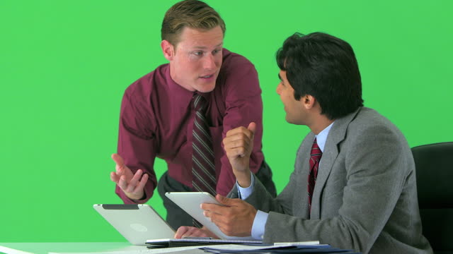 two businessmen working with tablets on greenscreen