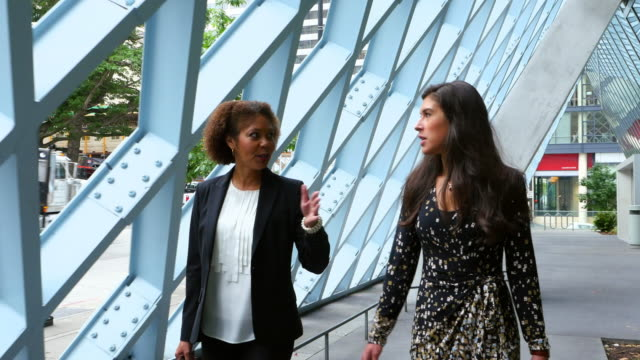 MS TS Two businesswomen in discussion while walking outside of office building
