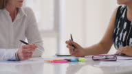 CU Two businesswomen work at a meeting table