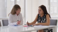 MS Two businesswomen work at a meeting table