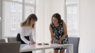 WS Two businesswomen work at a meeting table