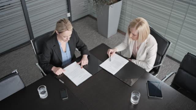CS zwei kaukasischen Geschäftsfrauen sitzen im Konferenzraum und durchläuft die Unterlagen auf dem Tisch