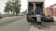Two caucasian men unload milk truck parked on permeable pavement in Chicago