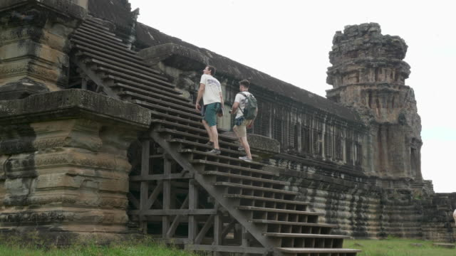 Two Caucasian Tourists ascending Angkor Wat Temple