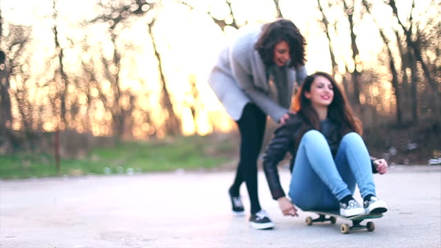 Two cheerful friends with skateboard having fun