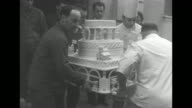 Two chefs and two others gingerly carry the base of an elaborate wedding cake through a door / a crown shaped wedding topper is carried / pan down...