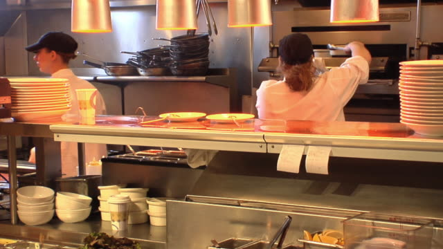 MS Two chefs preparing food in restaurant's kitchen / Chelsea, Michigan, USA