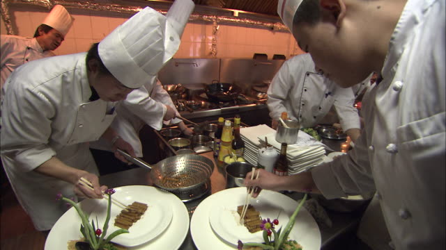 Two chefs put the finishing touches on two plates of food.