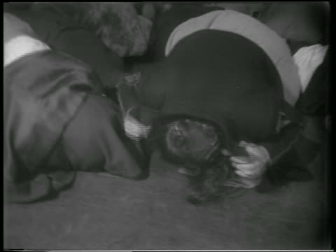 B/W 1951 two children crouched on floor with jackets over heads in civil defense drill / NYC / news