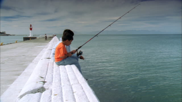 Two children fishing off side of pier with lighthouse in background, Western Cape, South Africa Available in HD.