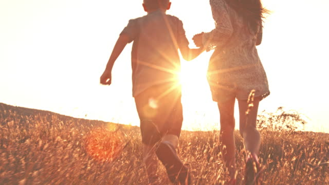 Two children holding hands, running together outdoors