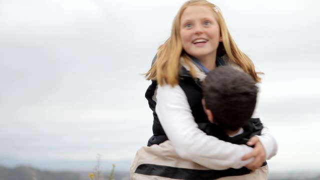 Due bambini abbracciare, spinning e ridere.