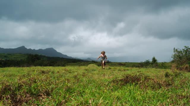 two children running through a field