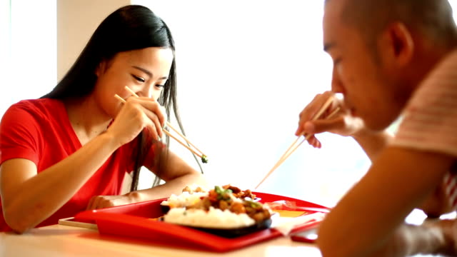 Two Chinese people eating in a restaurant.