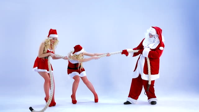 Two Christmas girls and Santa Claus pull a rope