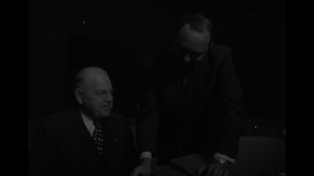 Two close shots of US Ambassador to UN Warren Austin sitting and talking to Secretary General of UN Trygve Lie of Norway standing next to him / CU...