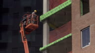 Two construction workers use high rise lift to work on building exterior.