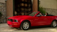 WS Two couples driving up to winery entrance in red convertible / Paso Robles, California, USA