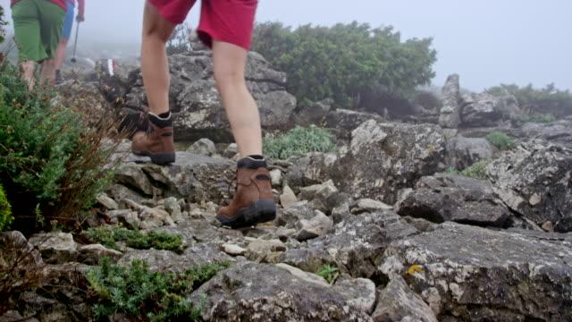 Twee koppels lopen op een mistige berg op een rotsachtige parcours