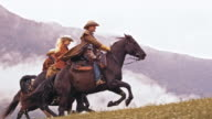 SLO MO DS Two cowboys and cowgirl riding galloping horses