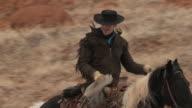 SLO MO MS PAN Two cowboys riding horses / Shell, Wyoming, USA