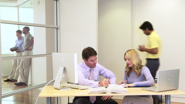Two coworkers at desk in busy office