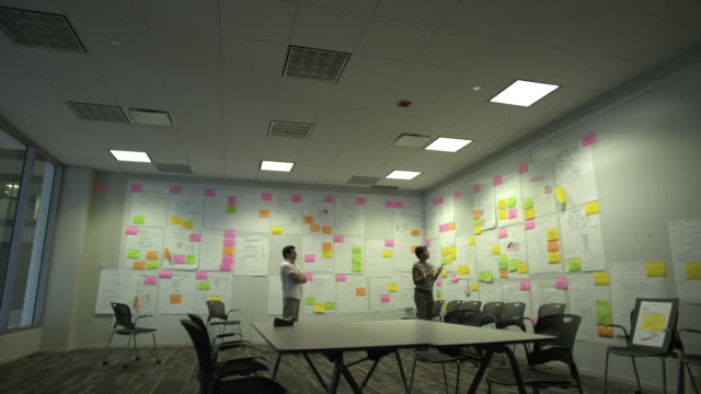 WS PAN Two coworkers brainstorm in creative conference room, Chicago, Illinois, USA