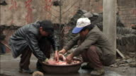 MS Two crouching men handling animal entrails in a bowl/ Guiyang, China