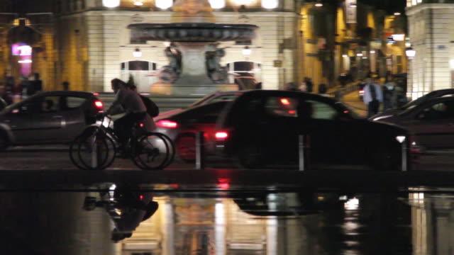 WS PAN Two cyclist at night on Bordeaux city centre promenade in front of Place de la Bourse / Bordeaux, Aquitaine, France.