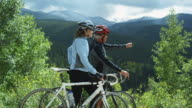 two cyclists looking out across a mountain view