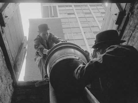 Two draymen lower a beer barrel into a cellar