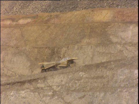 Two dumper trucks passing on pit pathway one labours uphill laden with rocks the other speeds downhill empty toward the quarry floor Kalgoorlie Australia