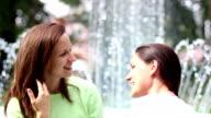 Two emotional girls near a fountain