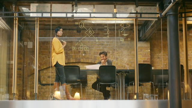 Two employees work on a project in modern office