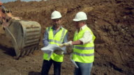 MS PAN Two engineers discussing plans on construction site with earth-moving machinery working in the background / Malaga, Andalusia, Spain