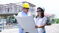 Two engineers on construction site with plan