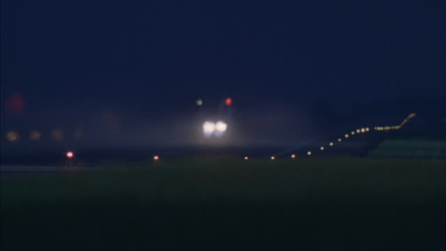 Two F15 fighter jets are taking-off from an air force base runway into the dark sky.