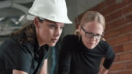 Two female architects discussing the plans on the table at the construction site and using a laptop