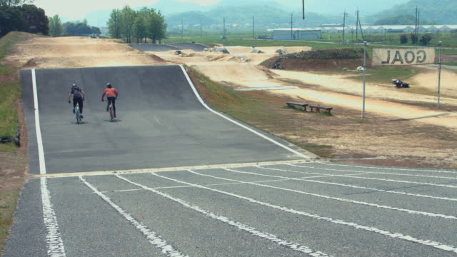 Two female athletes racing around a BMX track