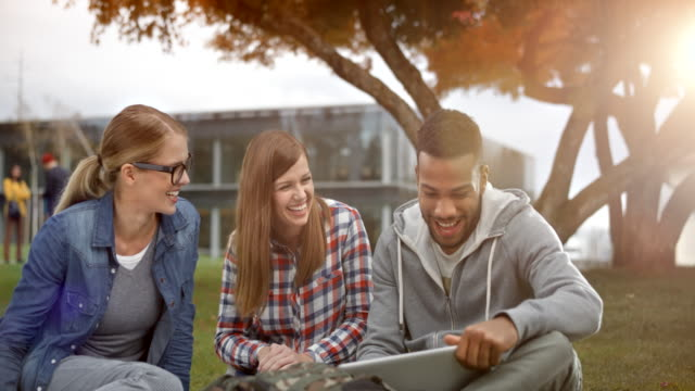 Two female Caucasian student laughing as they sit in the park with their multi ethnic male friend who is holding a laptop