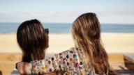 Two female friends embracing at bar by the beach in the South of France.