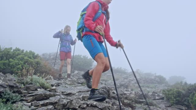 Twee vriendinnen wandelen van de berg in zware mist
