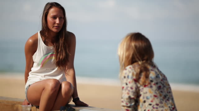 Two female friends looking serious, talking at the beach in the South of France.