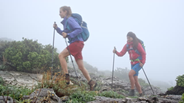 Twee vrouwelijke wandelaars lopen de mistige berg op een rotsachtige parcours