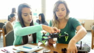 Two female Hispanic teenagers work together on robotics project at STEM school