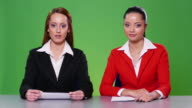 4K Two female newscasters on green background